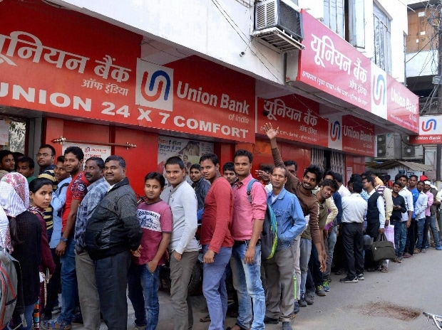 People stand in a long queue to withdraw money at an ATM in Allahabad