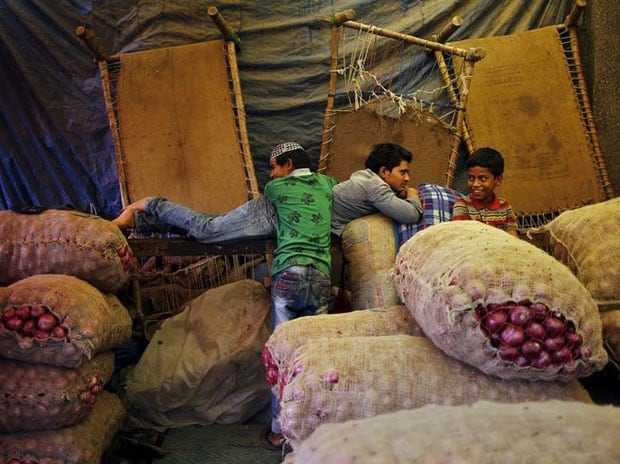 People rest next to stacked sacks of onions at a wholesale vegetable market in New Delhi. File Photo: Reuters