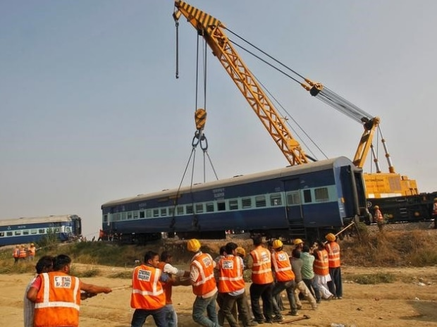 Rescue workers search for survivors at the site of a train derailment in Pukhrayan, south of Kanpur