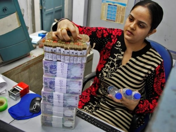 A cashier stacks Indian currency notes inside a bank in Chandigarh (Photo: Reuters)