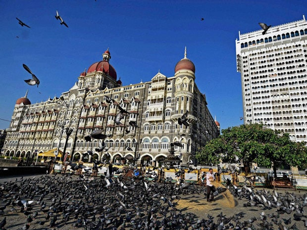 A man feeds pigeons outside the Gateway of India and Taj hotel on the eve of the eighth anniversary of 26/11 terror attack n Mumbai. Photo: PTI