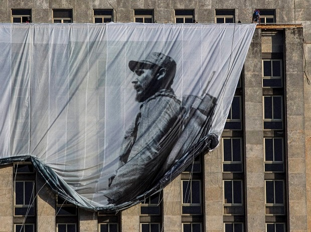 Men hang a giant banner with a picture of Cuba's late leader Fidel Castro as a young revolutionary, from the Cuban National Library building in Havana