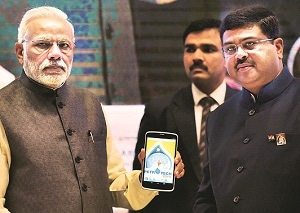 Prime Minister Narendra Modi shows the Petrotech app as MoS for Petroleum & Natural Gas (independent) Dharmendra Pradhan looks on at the Petrotech summit, in New Delhi, on Monday. Photo: PTI