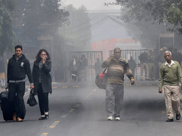 Passengers walk on a cold foggy morning at the New Delhi Railway Station in New Delhi. Photo: PTI