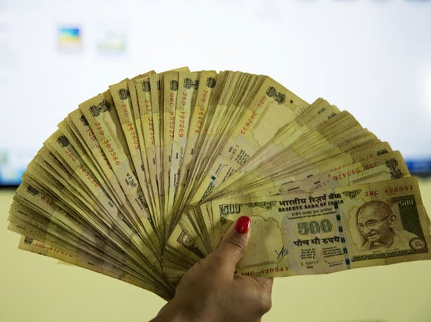 A woman holding old Rs 500 notes. Photo: Shutterstock