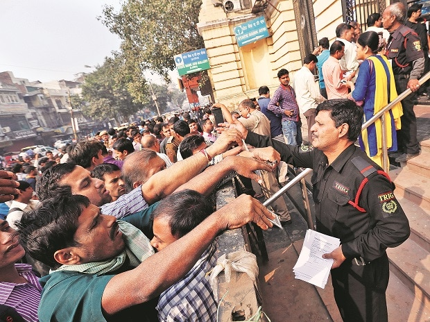 People queue up at a bank to exchange demonetised notes in New Delhi