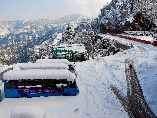 A man walks on snow covered road as vehicles stuck in snow after heavy snowfall in Shimla