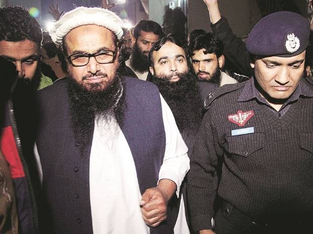 A Pakistani police officer escorts Hafiz Saeed (left), Chief of Pakistan's religious group Jamaat-ud-Dawa, outside the party's headquarters in Lahore, Pakistan, on Monday. File Photo: PTI