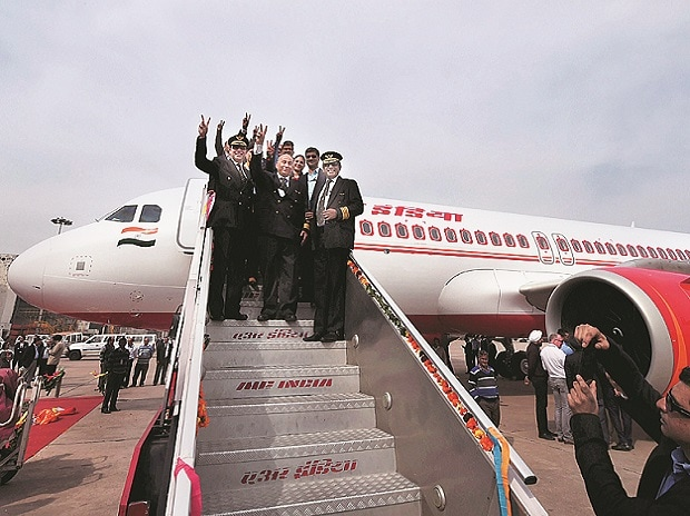 Officials of Airbus India and Air India show victory sign as first Airbus 320 neo plane arrives at Avionics Complex, Air India hangar IGI in New Delhi on Thursday. Photo: PTI