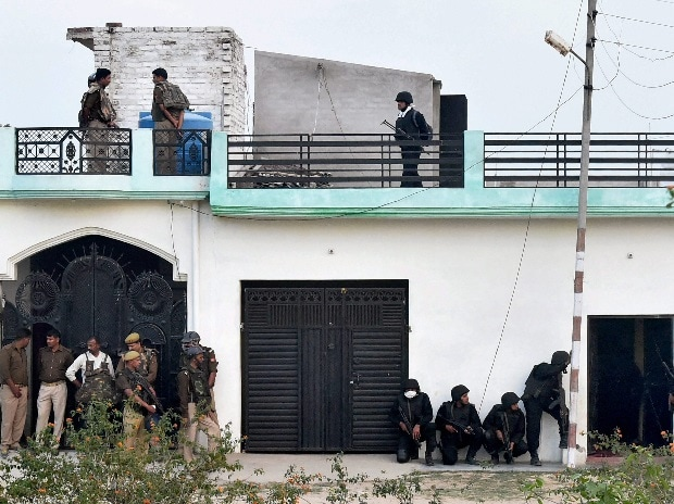 Uttar Pradesh Anti Terror Squad personnel take positions during their operation against a suspected terrorist holed up inside a building in the Thakurganj area of Lucknow