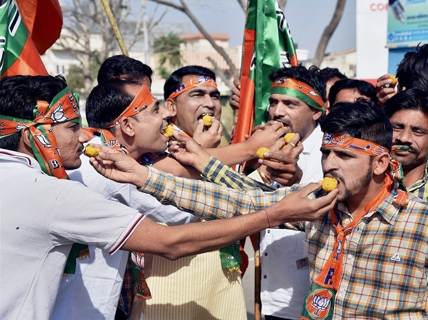 BJP supporters celebrate as early trends show the party's thumping win in the UP Election Results assembly polls