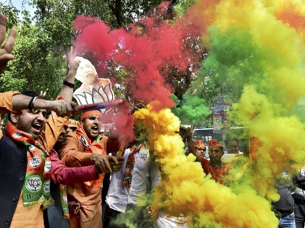BJP supporters and workers celebrate the party's victory in the assembly elections with colours, at party headquarters in New Delhi