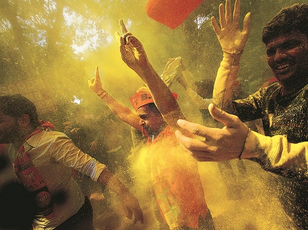 Bharatiya Janata Party (BJP) workers celebrate the victory of their party in Uttar Pradesh and Uttarakhand, in New Delhi on Saturday.