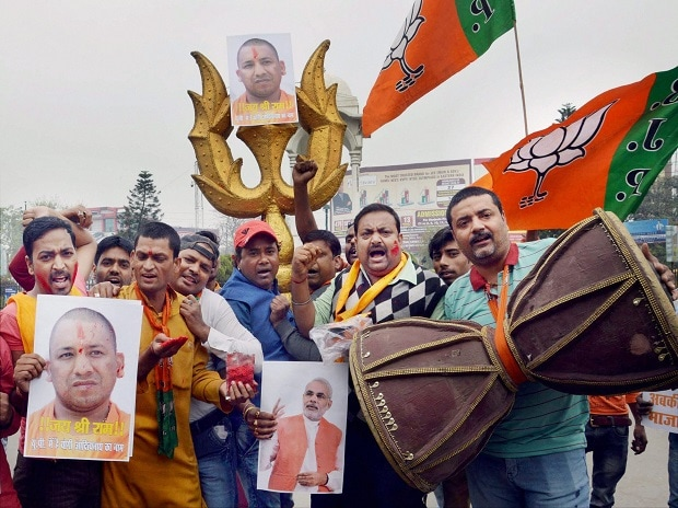 Bharatiya Janata Party workers celebrate the swearing-in of Yogi Adityanath as UP Chief Minister