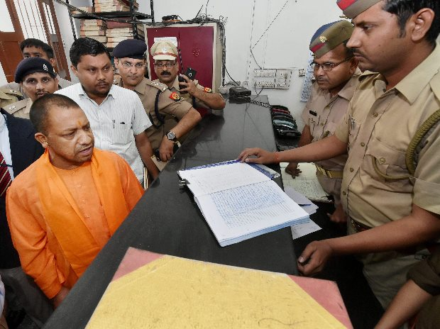 UP Chief Minister Yogi Adityanath speaking with a police personnel during a surprise visit at the Hazratganj police station in Lucknow (Photo: PTI)