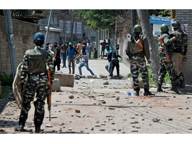 Youth throw stones on Security forces during clashes in Srinagar on Sunday. Four civilians where killed and more than two dozens were injured during the clashes. Photo: PTI