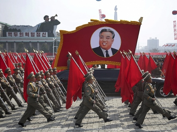 North Korean soldiers carry flags and a photo of late leader Kim Il Sung as they march across Kim Il Sung Square during a military parade
