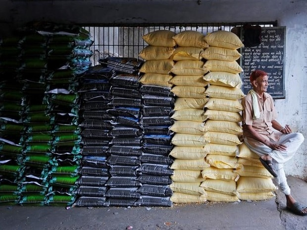 A labourer sits on sacks of food grains while waiting for customers at a wholesale market in Ahmedabad