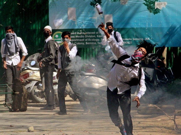 A student throwing stones on police amid heavy tear smoke during a clash with police outside SP college in the vicinity of Lal Chowk in Srinagar