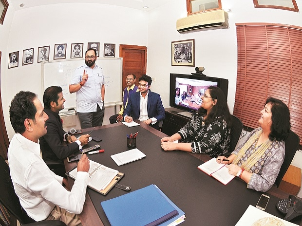 Rajeev Chandrasekhar (centre) with his policy research team at his office in New Delhi. Also seen is his Bengaluru team coordinating through video-conferencing