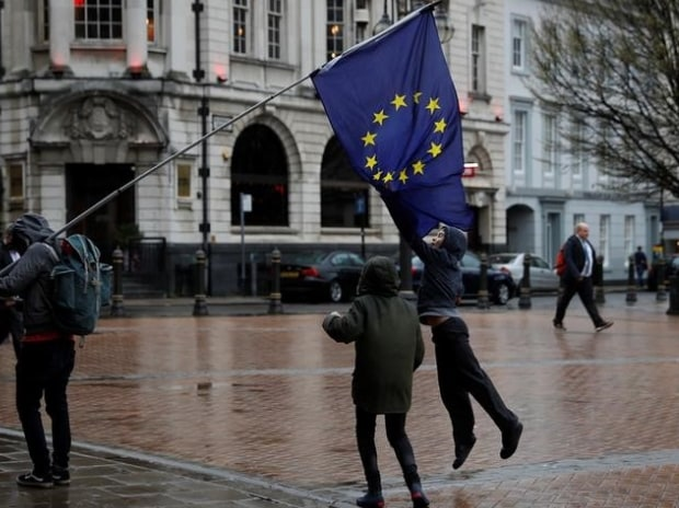 Children jump up to grab a European Union flag during an anti-Brexit demonstration after Britain's Prime Minister Theresa May triggered the process by which the United Kingdom will leave the Euopean Union, in Birmingham, Britain