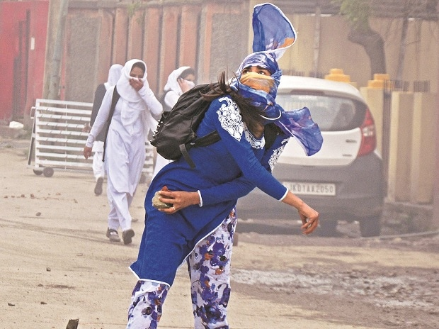 A girl throws a stone at security personnel during clashes in the vicinity of Lal Chowk in Srinagar. Photo: PTI