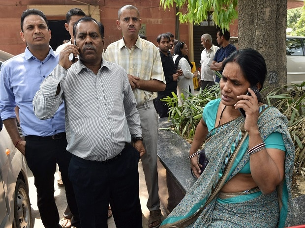 Nirbhaya's parents talk on phone at the Supreme Court in New Delhi on Friday. The apex court has confirmed death sentence for the four convicts of Nirbhaya gang rape case who raped and tortured the 23-year-old medical student on a moving bus in Delhi