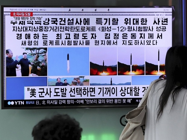 Woman walks by a TV news program showing images of North Korean leader Kim Jong Un and the missile launch, published in the country's Rodong Sinmun newspaper, at Seoul Railway station in Seoul, South Korea. File Photo: PTI