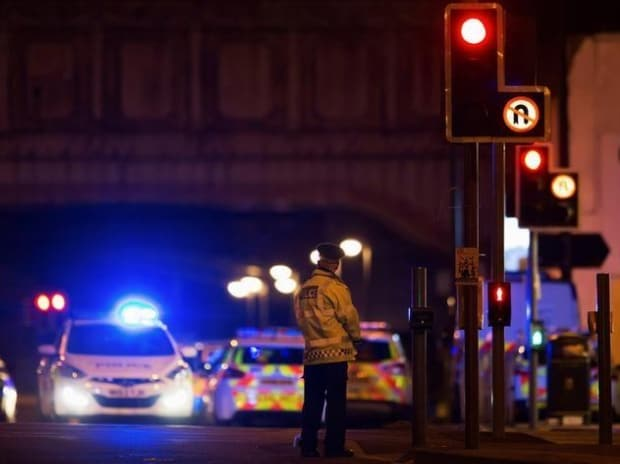 Police vehicles and a police officer are seen outside the Manchester Arena, where US singer Ariana Grande had been performing in Manchester, northern England, Britain