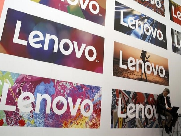 man uses his laptop next to Lenovo's logos. Photo: Reuters