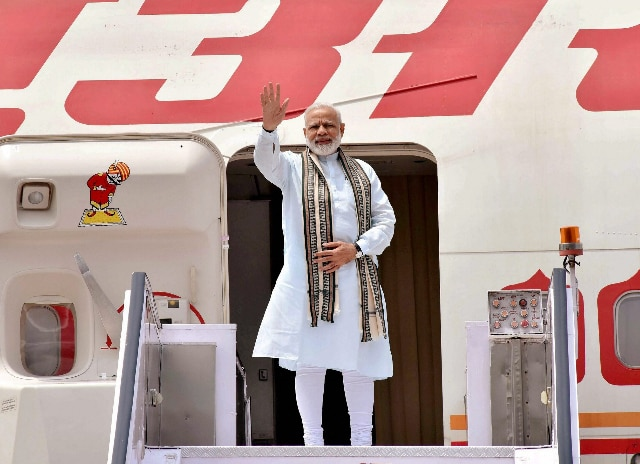 Prime Minister Narendra Modi waves before his departure from New Delhi on Monday for his visit to Germany, Spain, Russia and France. PTI Photo