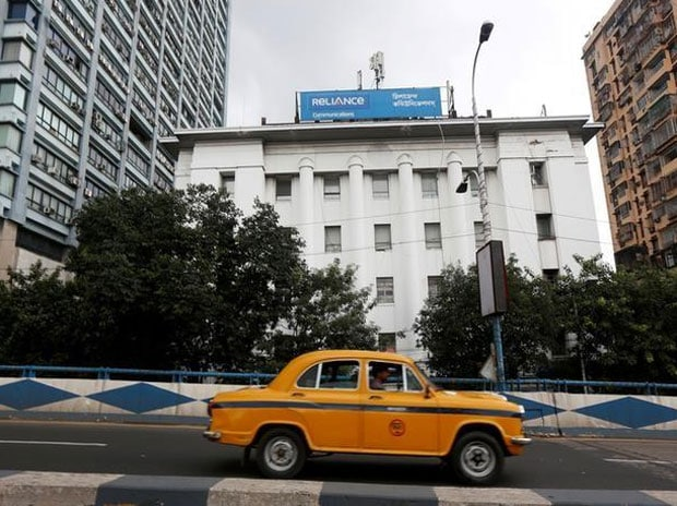 A taxi drives past a Reliance Communications ...