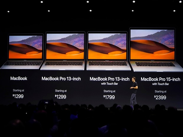 John Ternus, Vice President, Mac and iPad Hardware Engineering speaks under a graphic of price points for the Macbook laptop family during Apple's annual world wide developer conference (WWDC) in San Jose, California, U.S