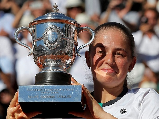 Latvia's Jelena Ostapenko holds the cup after defeating Romania's Simona Halep in their final match of the French Open tennis tournament at the Roland Garros stadium
