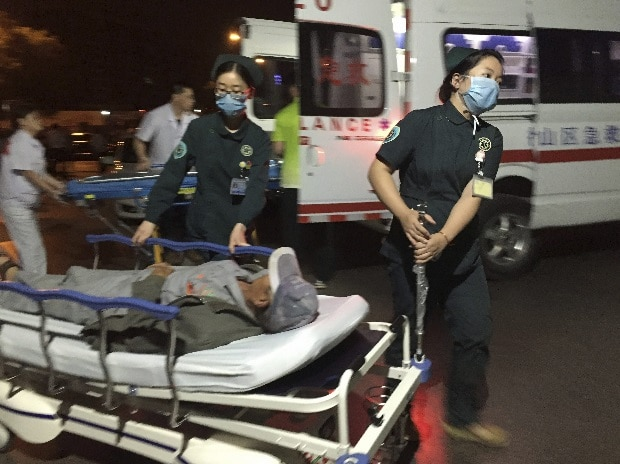 In this photo released by China's Xinhua News Agency, medical workers transport a person injured in an explosion outside a kindergarten into a hospital in Fengxian County in eastern China's Jiangsu Province early Friday