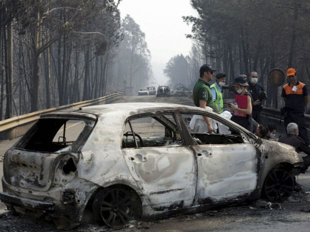 Police investigators stand by a burnt car on the road between Castanheira de Pera and Figueiro dos Vinhos, central Portugal, Sunday, June 18 2017. Many of the victims in the forest fire were trapped in their cars as flames swept over a road. Photo: A