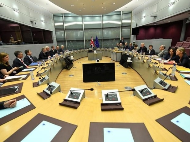 Britain's Secretary of State for Exiting the European Union David Davis and his delegation sit across from European Union's chief Brexit negotiator Michael Barnier and his delegation at the start of their first day of talks at the European Commission