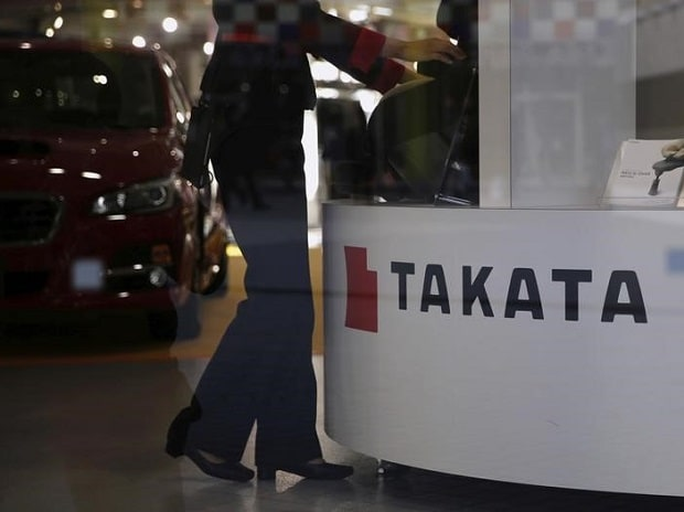 File photo: A woman stands next to a logo of Takata Corp at a showroom for vehicles in Tokyo, Japan