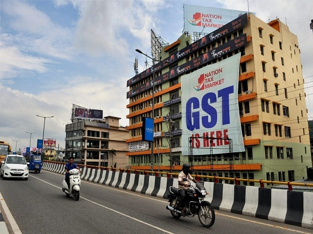 Vehicles move past a huge GST poster on the wall of a building, in Guwahati on Friday. Photo: PTI