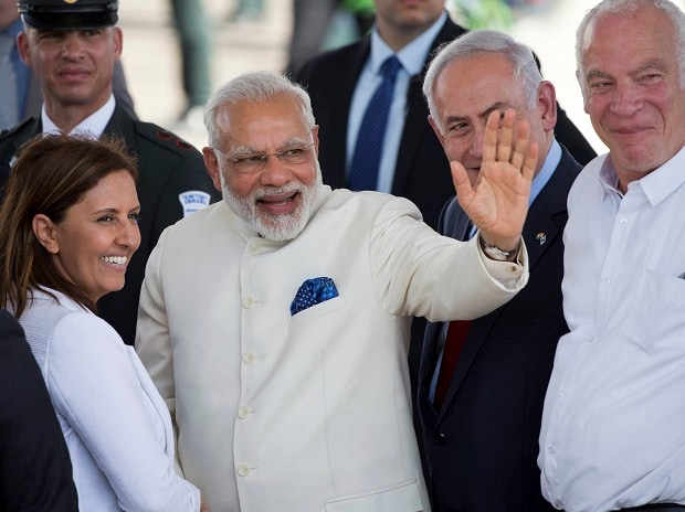 Indian Prime Minister Narendra Modi, centre, accompanied by Israeli Prime Minister Benjamin Netanyahu, right, waves during welcome ceremony upon arrival in Ben Gurion airport near Tel Aviv, Israel. Photo: PTI