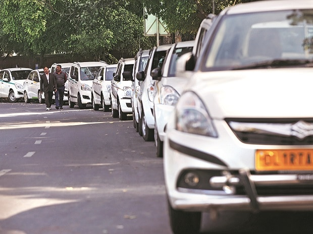 Drivers of Uber and Ola walk next to their parked vehicles during a protest in New Delhi in February 2017. Photo: Reuters
