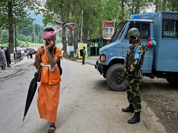 File of a sadhu proceeds towards the holy cave shrine as security personnel guard near Nunwan base camp on Tuesday, a day after the militants attacked Amarnath pilgrims onboard a bus.(Photo: PTI)