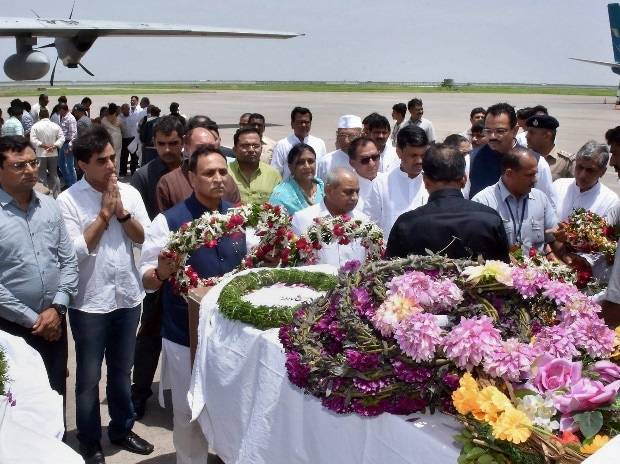 Gujarat Chief Minister Vijay Rupani and his deputy Nitin Patel paying tributes to Amatnath pilgrims who were killed Monday's militant attack in J & K, after their bodies were brought in an IAF plane at the airport in Surat on Tuesday. PTI Photo