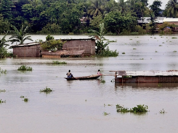 Villagers take services of a boat to reach to a safer place as incessant rains created a flood-like situation at Kureni Bori in Morigaon district of Assam on Wednesday. File Photo: PTI