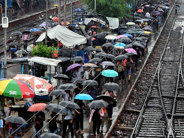 Stream of people open their umbrellas to save themselves from rain, as they walk beside the railway tracks at Ballygunge Junction station, in Kolkata