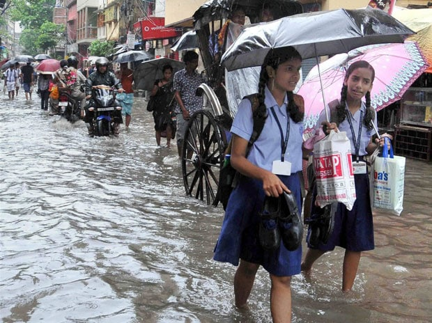 Schoolgirls wade through a flooded road after heavy downpour, in Kolkata