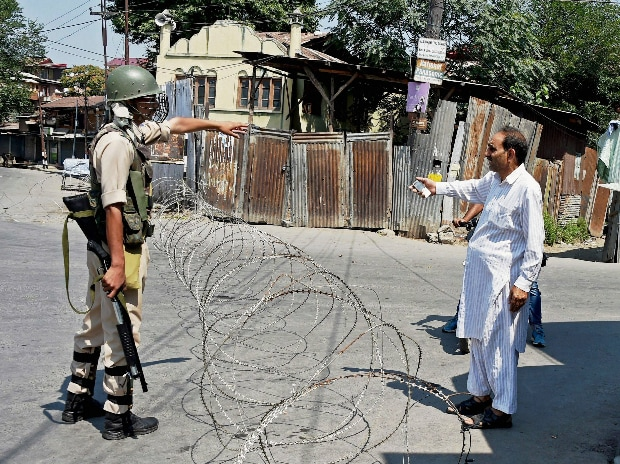 A Security jawan asks a man to change the route during restrictions in Downtown in Srinagar on Tuesday. (Photo: PTI)