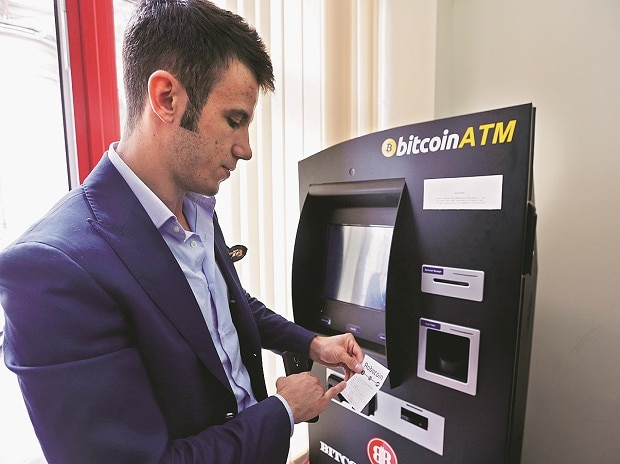 File photo of Bitcoin Romania CEO George Rotariu at a bitcoin ATM in Bucharest. A growing cohort of banking professionals are applying their talents toward buying or hawking cryptocurrencies such as bitcoins photo: reuters