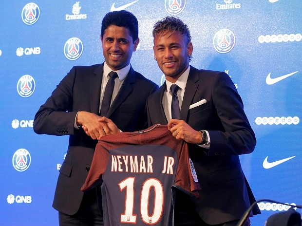 Brazilian soccer star Neymar holds his team shirt as he shakes with the chairman of Paris Saint-Germain Nasser Al-Khelaifi during a press conference in Paris. Photo: PTI/AP