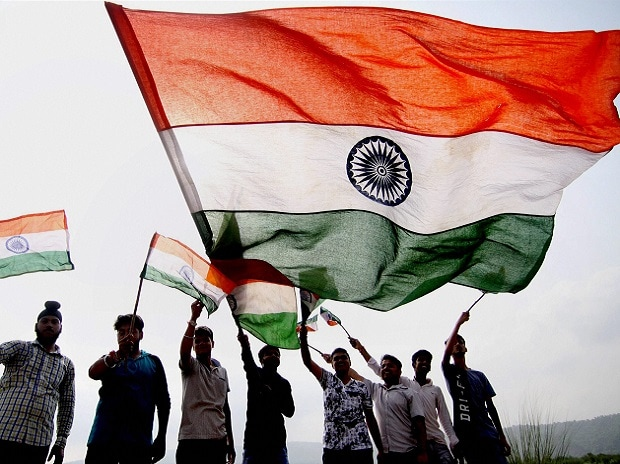 Youngsters wave the national flag ahead of India's Independence Day, in Jammu on Saturday. (Photo: PTI)